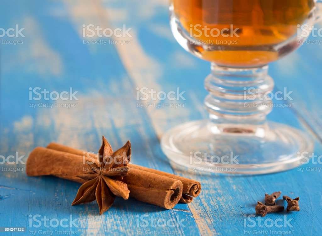Medical tea with spices in a glass mug on blue wooden boards. Nearby lie cinnamon sticks, carnations. royalty-free stock photo