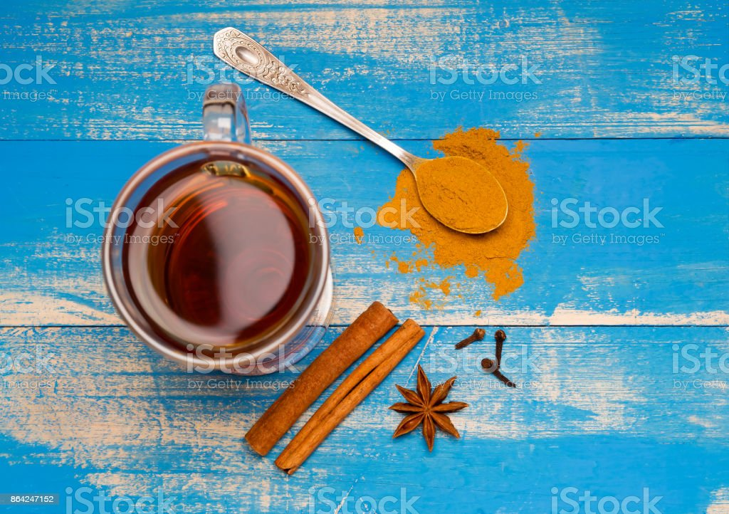 Medical tea with spices in a glass mug on blue wooden boards. Nearby lie cinnamon sticks, carnations and spoon with ground cardamom. Top of view. royalty-free stock photo