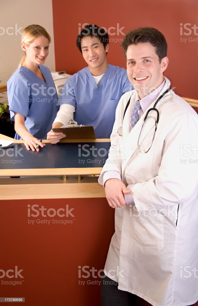 Male doctor with lab coat and stethoscope smiles in front of nurse...