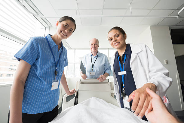 Medical team at patient's bedside, personal point of view stock photo