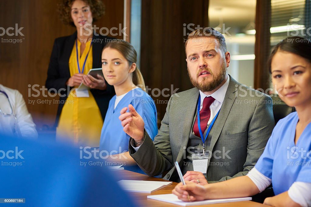 a senior doctor chats to his nursing team around a boardroom table....