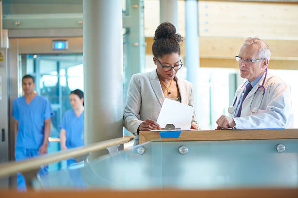 medical team discussing a case A suited woman and a male doctor wearing a lab coat stand on a stairwell of a modern hospital and discuss some case notes. The omwan could be an administrator or business woman . administrator stock pictures, royalty-free photos & images