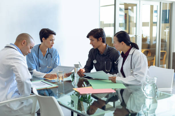 Medical team discussing with each other at the table in hospital stock photo