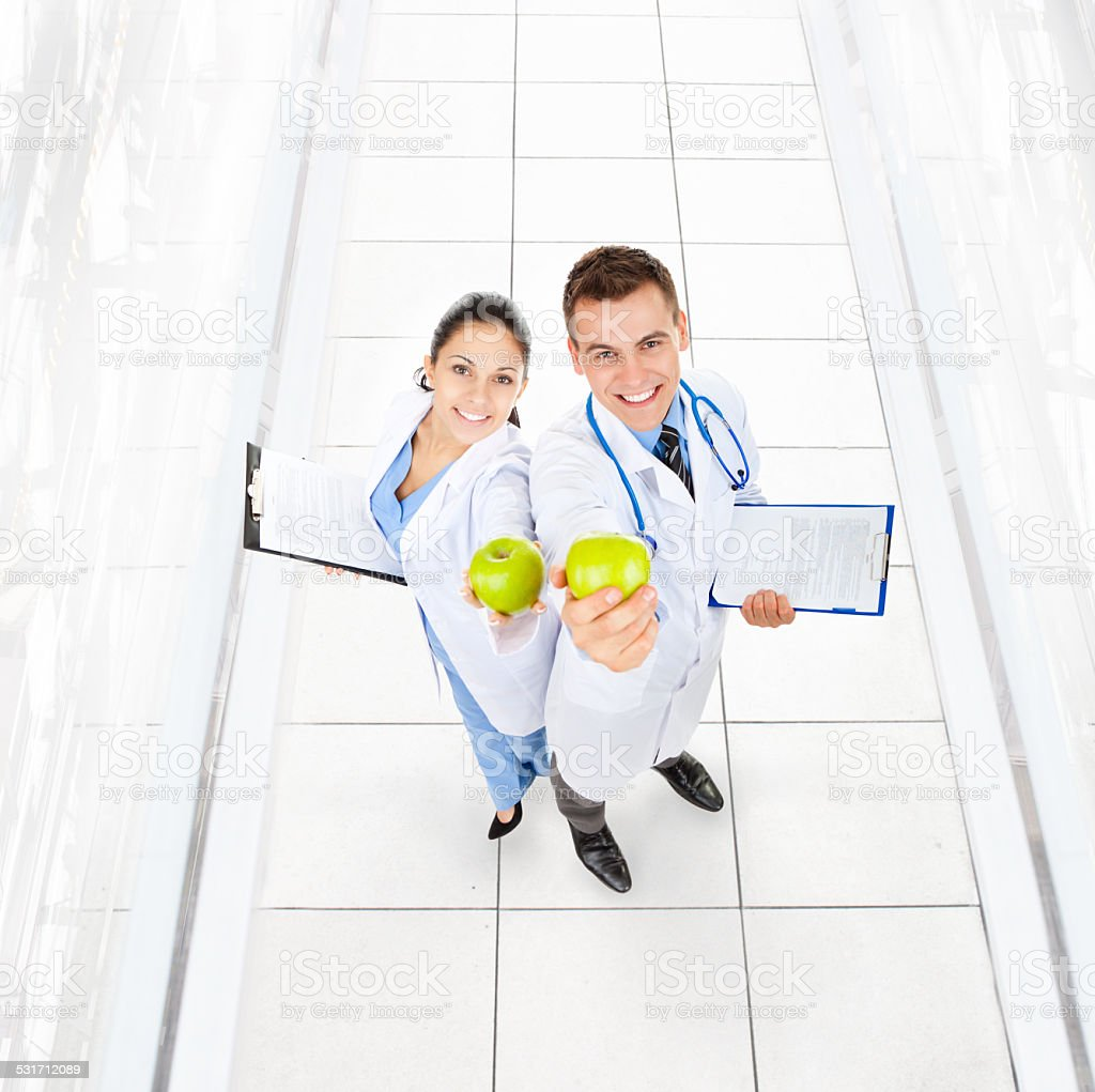 medical team doctor man and woman happy smile hold green fresh apple...