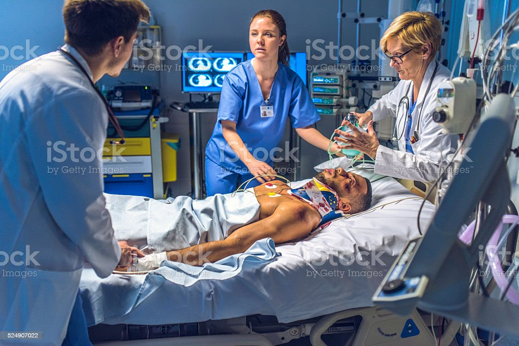 Medical team doing the CPR activites on injuried patient Female doctor holding a resuscitation bag on the face of a patient in emergency room. Accidents and Disasters Stock Photo