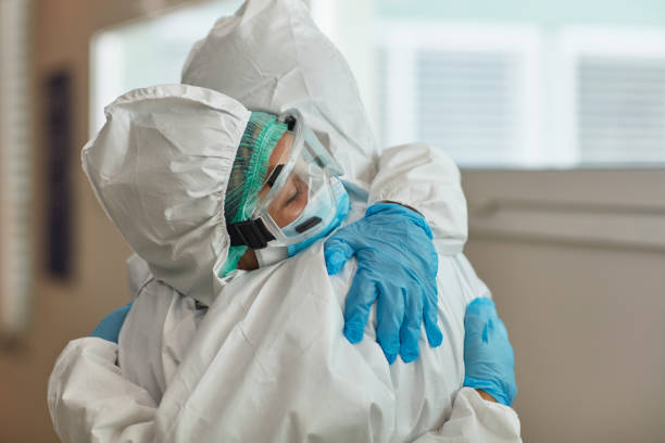 Medical Team in Protective Workwear Embracing in Support stock photo