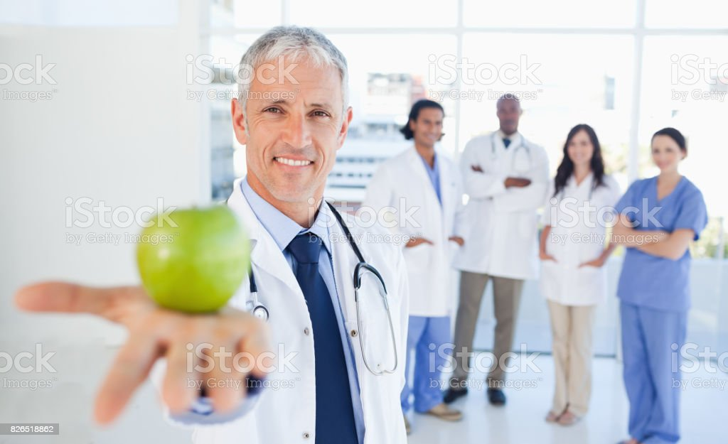 Medical team in the background looking at a doctor who is holding a green apple stock photo