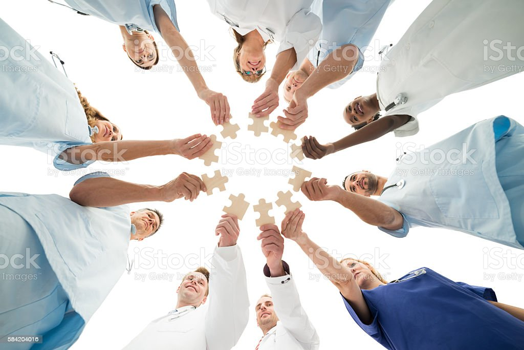 Medical Team Joining Jigsaw Pieces In Huddle stock photo