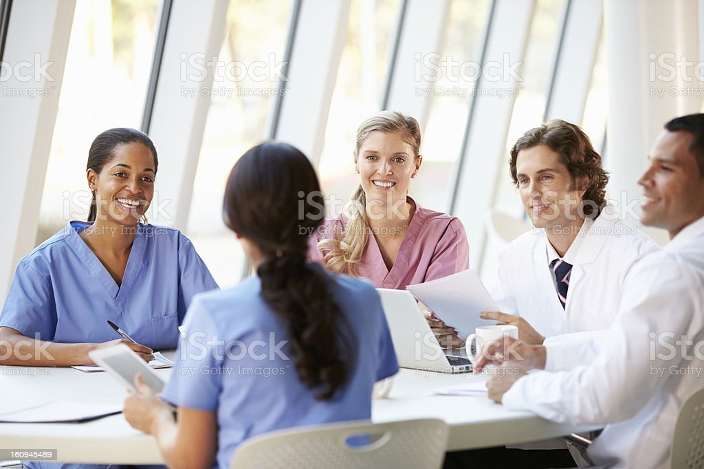 Medical Team Meeting Around Table In Modern Hospital stock photo