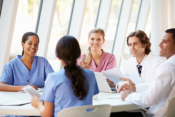 medical team meeting around table in modern hospital - organised group stock photos and pictures
