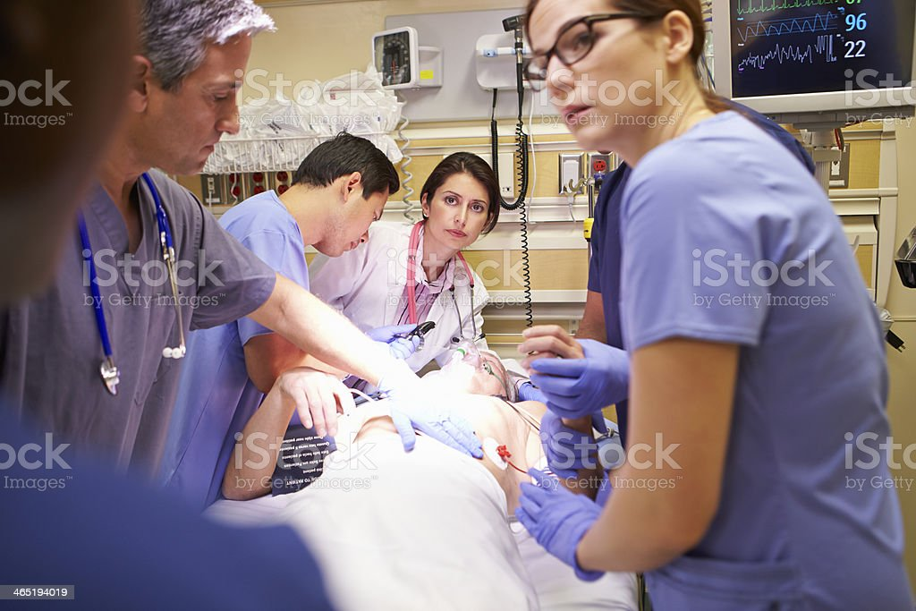 Medical team of five people working on a patient in ER stock photo