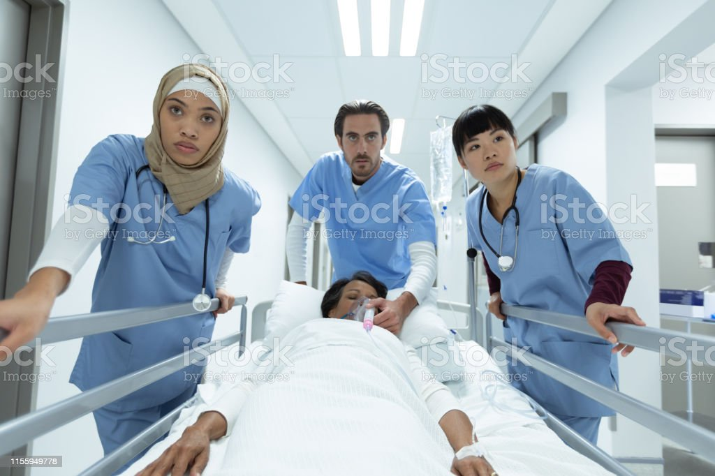 Front view of diverse medical team pushing emergency stretcher bed in...