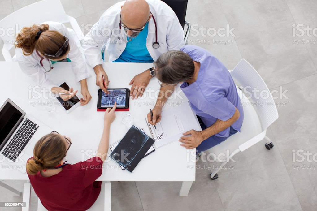 Medical team sitting and discussing at table stock photo