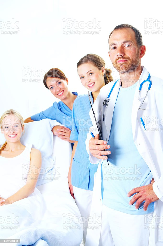 Medical team standing beside a patient in bed royalty-free stock photo
