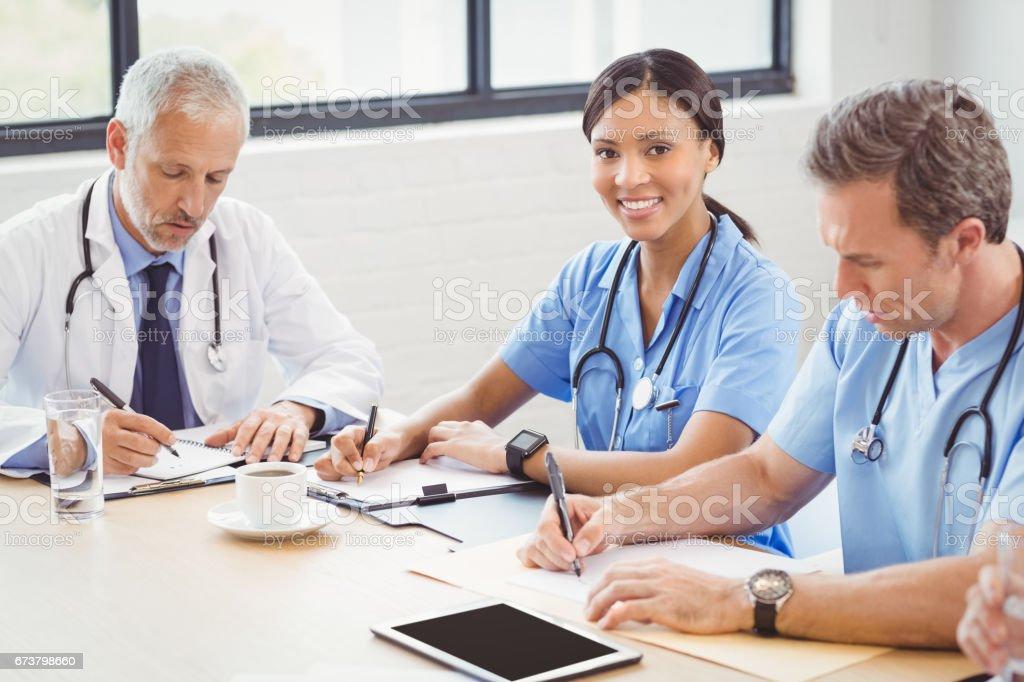 Équipe médicale rédigé un rapport dans la salle de conférence photo libre de droits