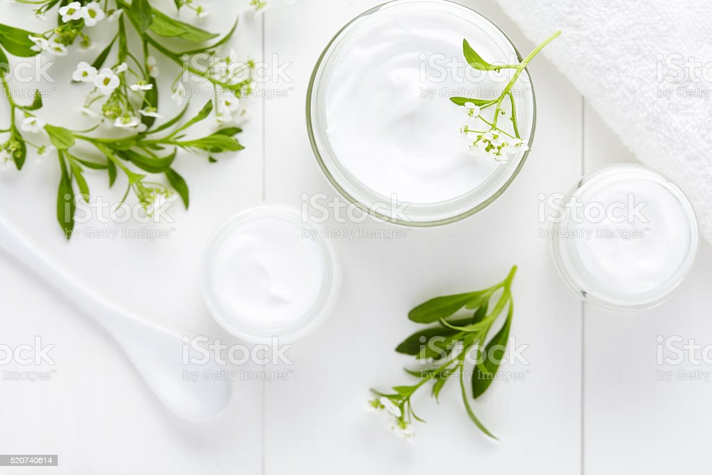 Medical therapy cosmetic cream with herbal flowers hygienic skincare product stock photo
