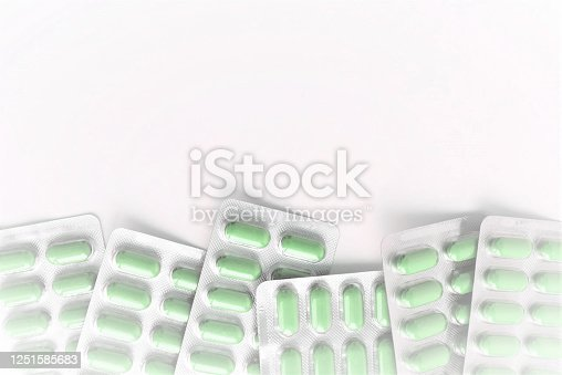 1087546614 istock photo medical therapy, on a white blurred background green capsules in blisters located below, drug treatment 1251585683