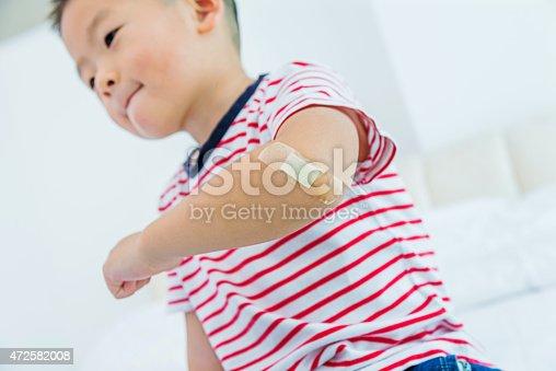 Asian boy getting band-aid.