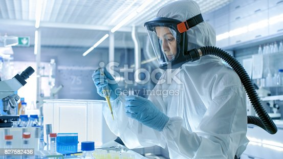 istock Medical Virology Research Scientist Works in a Hazmat Suit with Mask, She Uses Micropipette. She Works in a Sterile High Tech Laboratory, Research Facility. 827582436