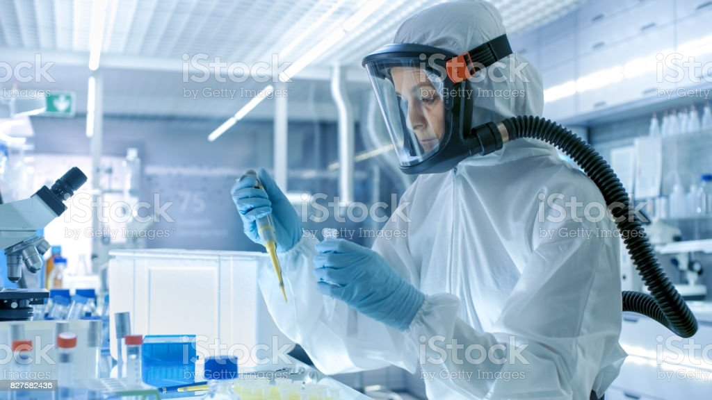 Medical Virology Research Scientist Works in a Hazmat Suit with Mask, She Uses Micropipette. She Works in a Sterile High Tech Laboratory, Research Facility. stock photo