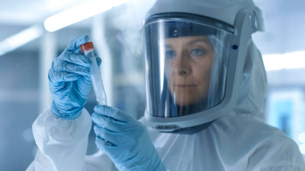Medical Virology Research Scientist Works in a Hazmat Suit with Mask, Inspects Test Tube with Isolated Virus String from Refrigerator Box. She Works in a Sterile High Tech Laboratory/ Research Facility. stock photo