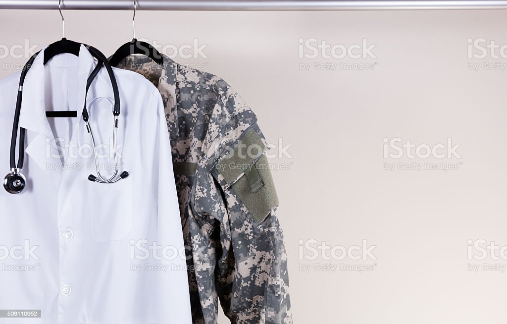 Medical white consultation coat and military uniform on hanger stock photo