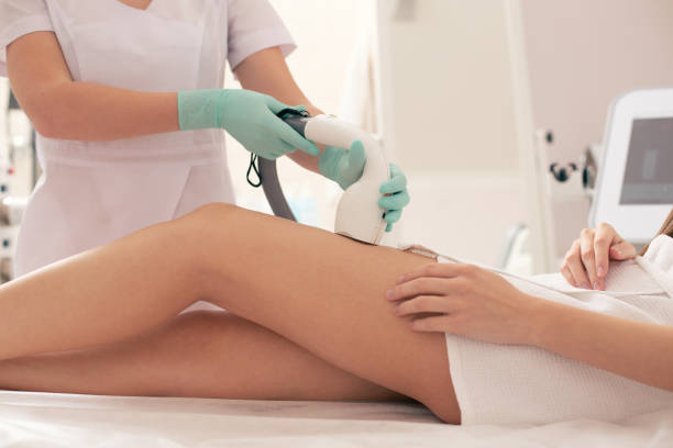Medical worker using vacuum suction for hair removal stock photo