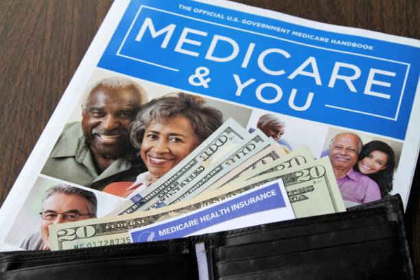 Medicare and Social Security cards with cash and Medicare handbook Medicare and Social Security cards with USA currency cash.  Cards and currency are protruding from an open wallet that lies on top of an official government printed Medicare Handbook. Health care and social welfare concept for seniors in the USA. medicare stock pictures, royalty-free photos & images