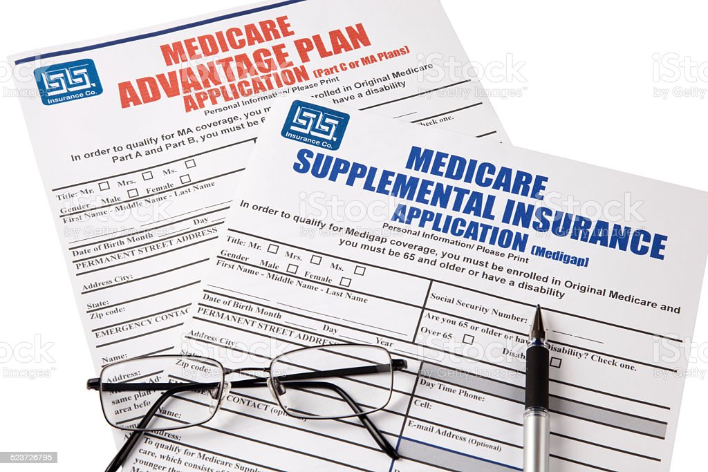 Medicare Applications with glasses and pen, isolated stock photo