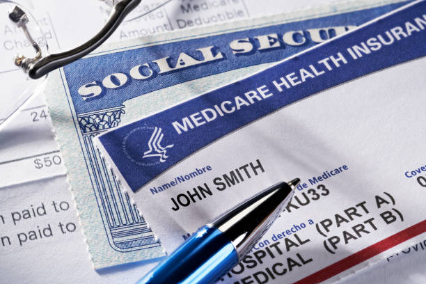 medicare health insurance and social security card on medical report docuement - social security check stock photos and pictures