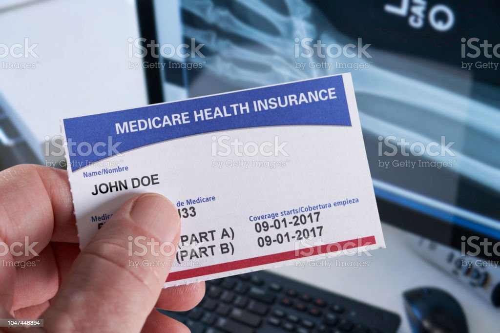 Medicare Health Insurance Card in medical office with Xray and hand