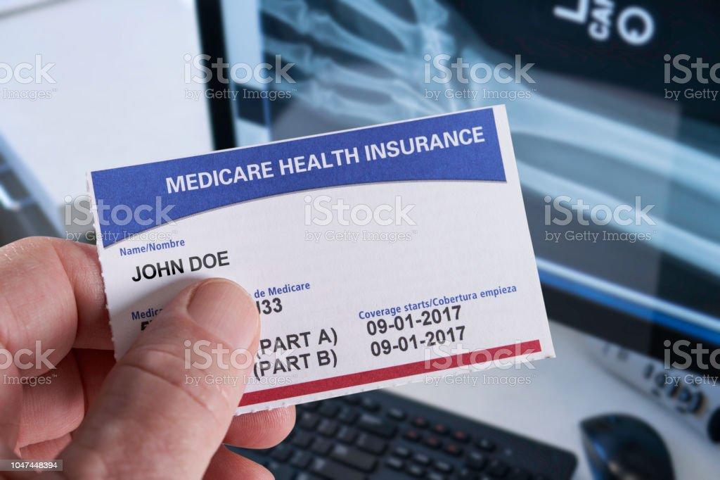 Medicare Krankenversicherungskarte in Arztpraxis mit Xray und Hand halten – Foto