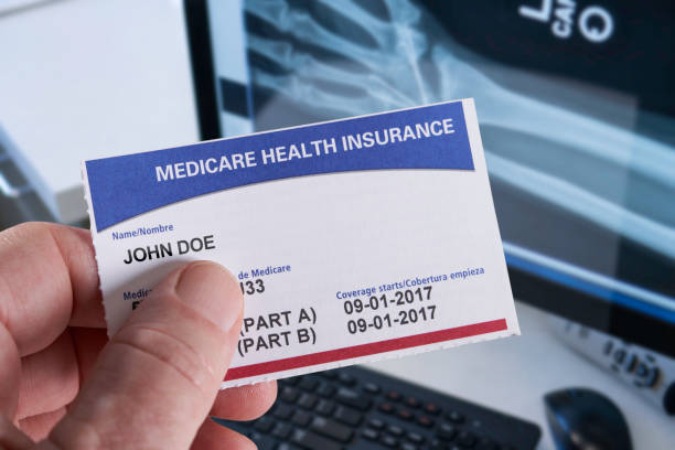 Medicare Health Insurance Card in medical office with Xray and hand holding Medicare Health Insurance Card in medical office with Xray and hand playing card stock pictures, royalty-free photos & images