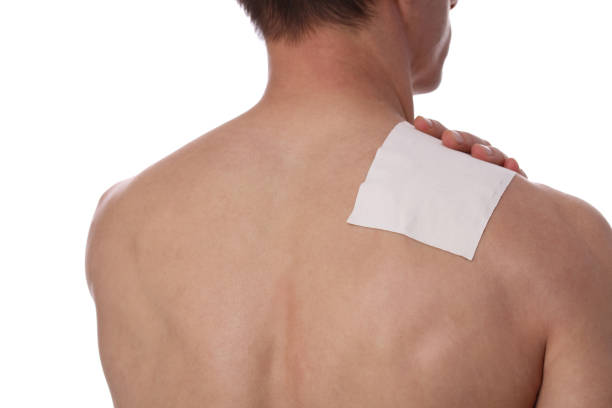 Medicated pain relief patch, plaster. man with back, neck pain. Pain relief and health care concept isolated on white. stock photo
