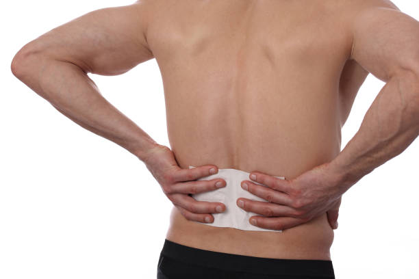 Medicated pain relief patch, plaster. man with back pain. Pain relief and health care concept isolated on white. stock photo