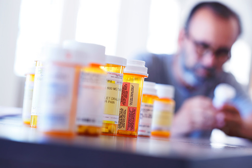 A large group of prescription medication bottles sit on a table in front of a man who is holding and looking at one of the pill bottles out of focus in the background.  The image is photographed with a very shallow depth of field with the focus being on the pill bottles in the foreground.