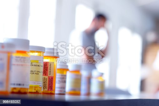 A large group of prescription medication bottles sit on a table as a man in the background stands with his hand on his head. The image is photographed with a very shallow depth of field with the focus being on the pill bottles in the foreground.