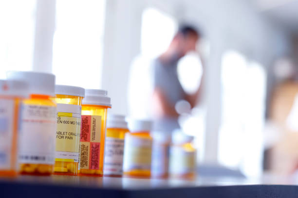 Medication Addiction A large group of prescription medication bottles sit on a table as a man in the background stands with his hand on his head. The image is photographed with a very shallow depth of field with the focus being on the pill bottles in the foreground. crisis stock pictures, royalty-free photos & images