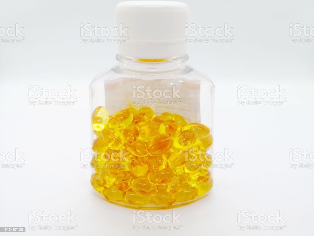Medication and healthcare concept. Many yellow capsules of Cod liver oil. isolated on white background, used to nourish body and increase appetite. Focus on foreground and copy space. stock photo