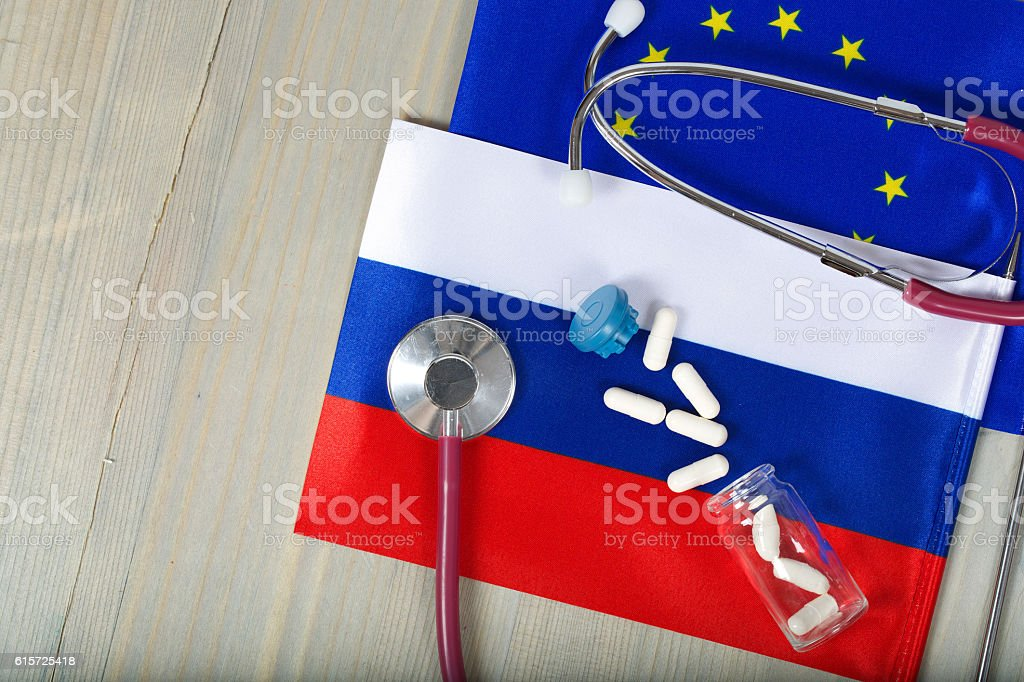 Medication and stethoscope on European and Russian flags stock photo