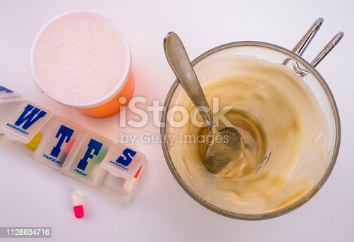Medication during breakfast, cup of coffee next to a pillbox, conceptual image, horizontal composition
