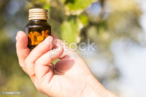Medication in senior hand, bokeh nature background