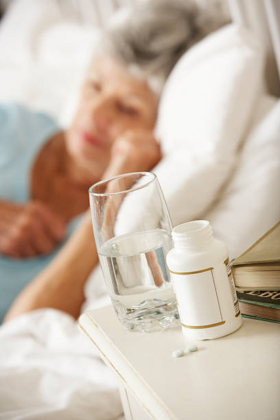 medication on bedside table of sleeping senior woman - sleeping pill stock photos and pictures