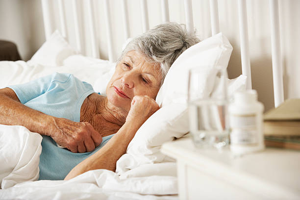 medication on bedside table of sleepless senior woman - sleeping pill stock photos and pictures