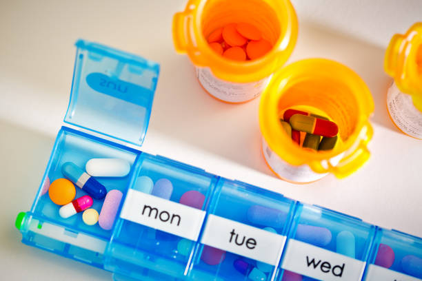 Medication Pill Box Pill Bottle with Prescription Drug, Cost of Healthcare A medication pill box daily chamber filled with a variety of prescription drug.  concept still life of medicine in healthcare, opioid social issue, and prescription drug abuse. medium group of objects stock pictures, royalty-free photos & images