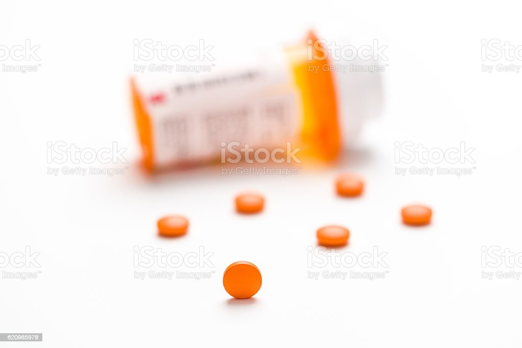Medication, pills spilling out, tight focus on single pill. stock photo