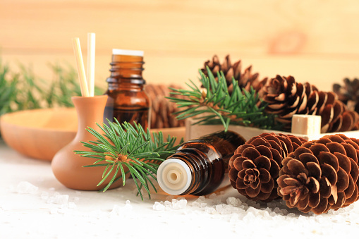 Medicinal amberglass dropper bottle with green fir-needle and cones, aromalamp diffuser for relaxing healthy spa.