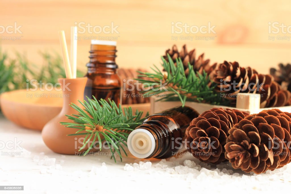Medicinal amberglass dropper bottle with green fir-needle and cones, aromalamp diffuser for relaxing healthy spa. stock photo