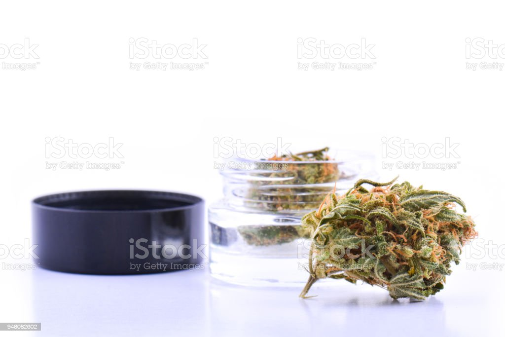 Medicinal marijuana cannabis in a bottle. Cannabis hemp products in jar. Cannabis weed bud on white background stock photo