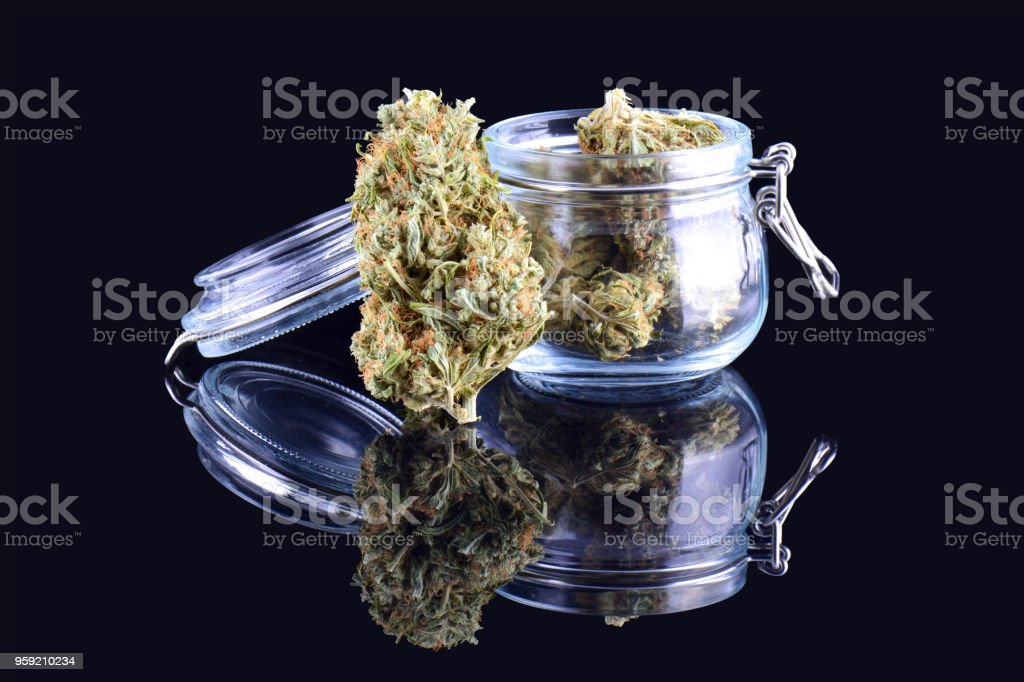 Medicinal marijuana cannabis in a bottle. Cannabis hemp products in jar. Cannabis weed bud isolated on black background stock photo